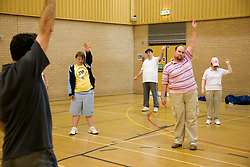 Day Service Assistant leading a group of service users with learning disabilities to do warm up exercises in the gym,