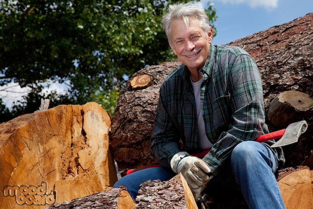 Smiling senior man sitting on logs