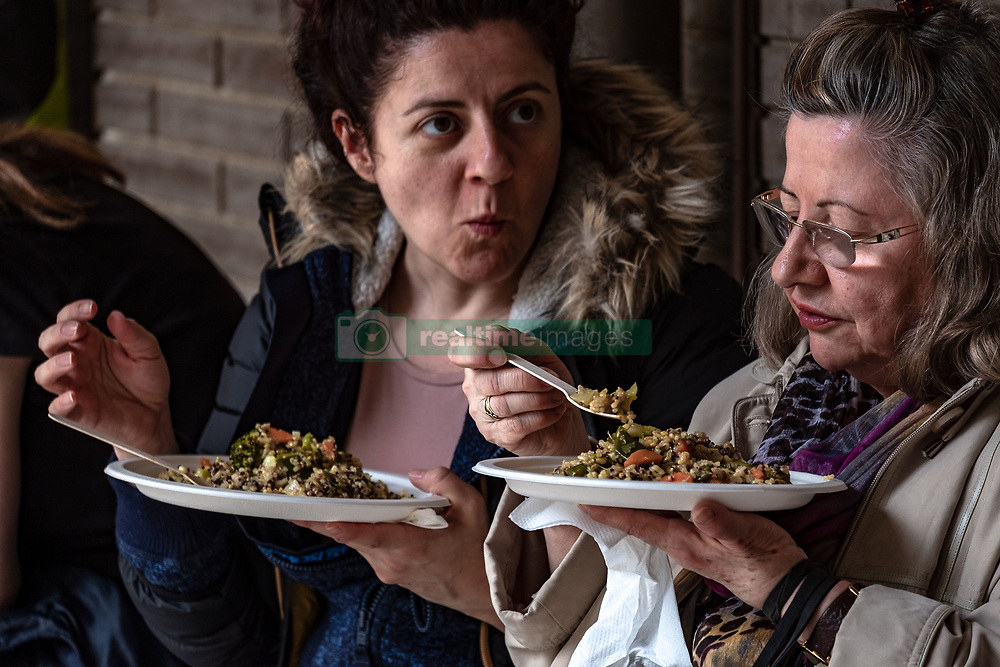 May 6, 2018 - Barcelona, Catalonia, Spain - Two women who visit BioCultura are seen at lunchtime inside the fairgrounds. BioCultura, the Organic Products Fair and Responsible Consumption celebrates its 25th anniversary. It will bring together over 700 exhibitors dedicated to the sectors of food bio, organic cosmetics, sustainable fashion, home safe, responsible tourism, crafts and NGOs. Parallel to the exhibition more than 400 activities will be held and is expected to exceed 72,000 visitors. It will be held from 3 to 6 May at the Palau Sant Jordi in Barcelona. (Credit Image: © Paco Freire/SOPA Images via ZUMA Wire)