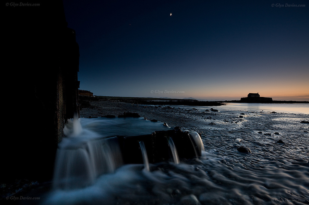 Water floods out from fields via a drainage outlet as a half moon rises in the sky above the church of Eglwys Cwyfan in the cove of Porth Cwyfan, West Anglesey, Wales