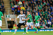 Germany defender Joshua Kimmich (6) tussles with Northern Ireland midfielder Corry Evans (13) during the UEFA European 2020 Qualifier match between Northern Ireland and Germany at National Football Stadium, Windsor Park, Northern Ireland on 9 September 2019.