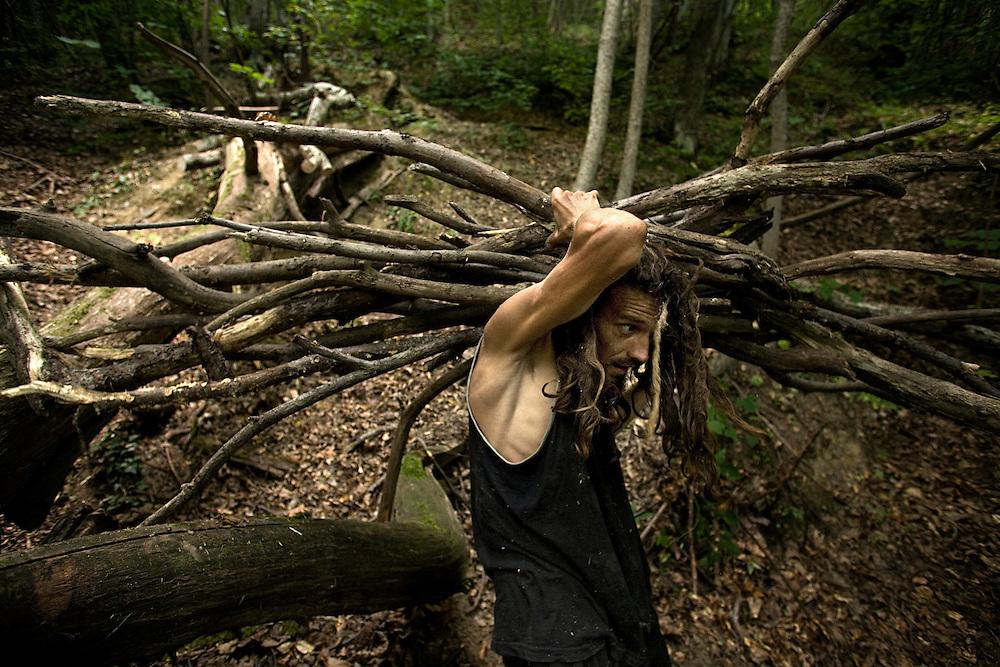 Carrying tree branches in the forest..Marco, a former italian manager who's given up on his career to embrace the wild life.
