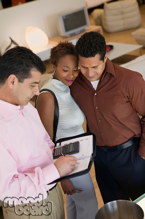 Salesman Calculating Purchase Amount of couple in furniture store high angle view