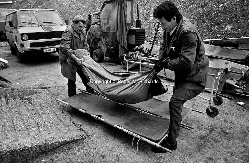 Morgue attendants lift the body of a 16-year-old girl killed on a Sunday morning when a Serb shell hit her house, Sarajevo, Bosnia-Herzegovina, February 1993. PHOTO BY ROGER RICHARDS