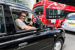A London black cab driver shows his support to the demonstration jamming the streets of Southwark in protest over the refusal to place a Black Cab taxi rank outside the entrance to The Shard.May 2013 London