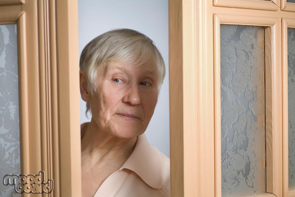 Elderly woman with short grey hair opening front door