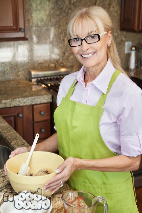 Portrait of a happy senior woman preparing food in kitchen