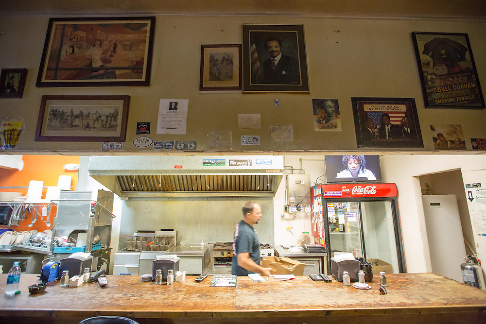 """A walking contradiction, Patrick Lanzo, owner of Georgia Peach Oyster Bar in Paulding County, Ga., works behind the bar there on July 2, 2015. Photos above the bar include portraits of Jesse Jackson and Martin Luther King. Jr. Lanzo, who says he is on the FBI's Terrorist Watchlist for many of the controversial things he has done, including placing a sign out front of his business that read """"Obama. A vision of a dream. James Earl Ray."""" Shot for a story about changes occurring in the South following a heightened national awareness and sensitivity concerning the Confederate battle flag. Photo by Kevin Liles for The New York Times"""
