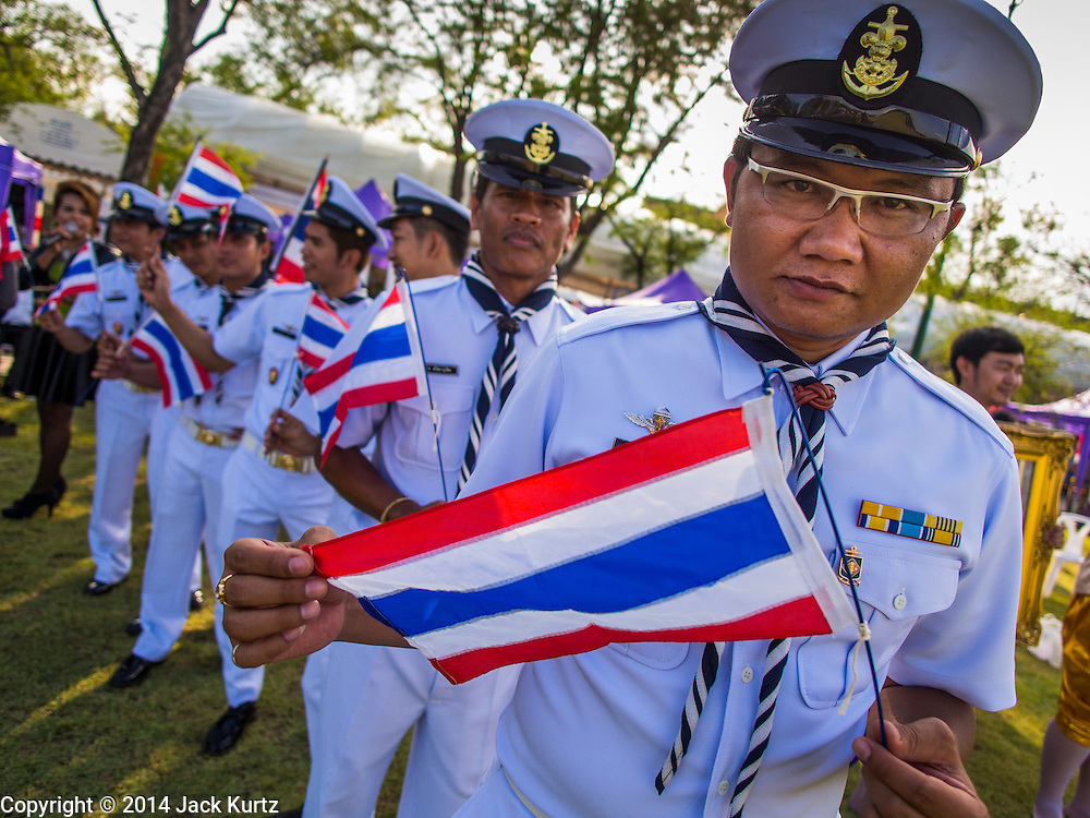 """24 JULY 2014 - BANGKOK, THAILAND: Thai Sea Scouts carry Thai flags in a patriotic parade at the happiness party in Bangkok. The Thai Junta is organizing a series of public events throughout Thailand meant to bolster public opinion. The events are called """"restoring happiness to the people"""" parties. They feature historic pageants, music, food, health checks and free haircuts. The party in Bangkok is on Sanam Luang, the Royal Parade Ground, which is near the Grand Palace and the Ministry of Defense.    PHOTO BY JACK KURTZ"""