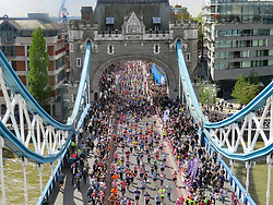 © Licensed to London News Pictures. 23/04/2017. LONDON, UK.  Crowds of marathon runners cross Tower Bridge, seen from the glass walkway of Tower Bridge, as runners reach the half way point.  Photo credit: Graham Long/LNP