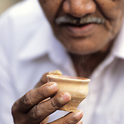 An old man holding a cley cup, a 'Kulhar', with hot chai near Sadar street in Kolakta. Cley cups are the 'paper cups' of India. An estimated 17 million (1.7 crore) kulhars are consumed in India every day.  There are proposals within the railway ministry to double the production of kulhars to over 30 million (3 crores) a day by making them more user-friendly and increasing their availability at railway stations and trains, but how far this move will be succesful waits to be seen. (According to the railway ministry; Times of India, February 2005)
