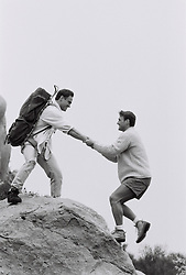 Hiker helping a man up a rock