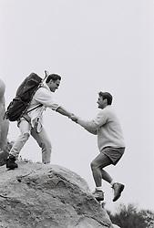 Hiker helping a man up a rock