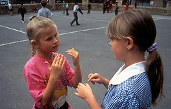 Hearing and hearing impaired children signing in primary school playground UK