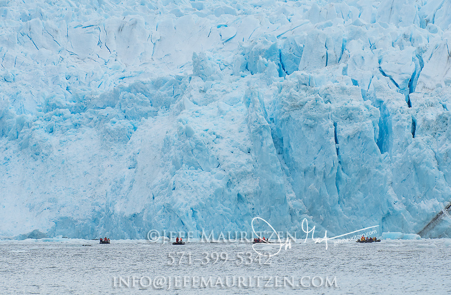 Expedition travelers aboard zodiac inflatable boats explore Garibaldi glacier national park in Chile.