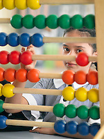 Elementary schoolgirl looking through abacus sitting in classroom