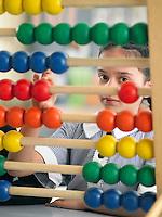 Elementary schoolgirl looking through abacus sitting in classroom