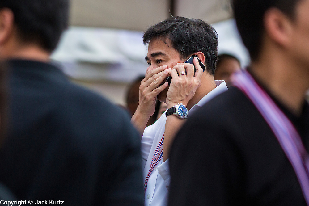 "15 NOVEMBER 2013 - BANGKOK, THAILAND: Former Thai Prime Minister ABHISIT VEJJAJIVA and leader of the Thai Democrat party, covers his mouth while he makes a mobile phone call at an anti-government protest in Bangkok. Tens of thousands of Thais packed the area around Democracy Monument in the old part of Bangkok Friday night to protest against efforts by the ruling Pheu Thai party to pass an amnesty bill that could lead to the return of former Prime Minister Thaksin Shinawatra. Protest leader and former Deputy Prime Minister Suthep Thaugsuban announced an all-out drive to eradicate the ""Thaksin regime."" The protest Friday was the biggest since the amnesty bill issue percolated back into the public consciousness. The anti-government protesters have vowed to continue their protests even though the Thai Senate voted down the bill, thus killing it for at least six months.     PHOTO BY JACK KURTZ"