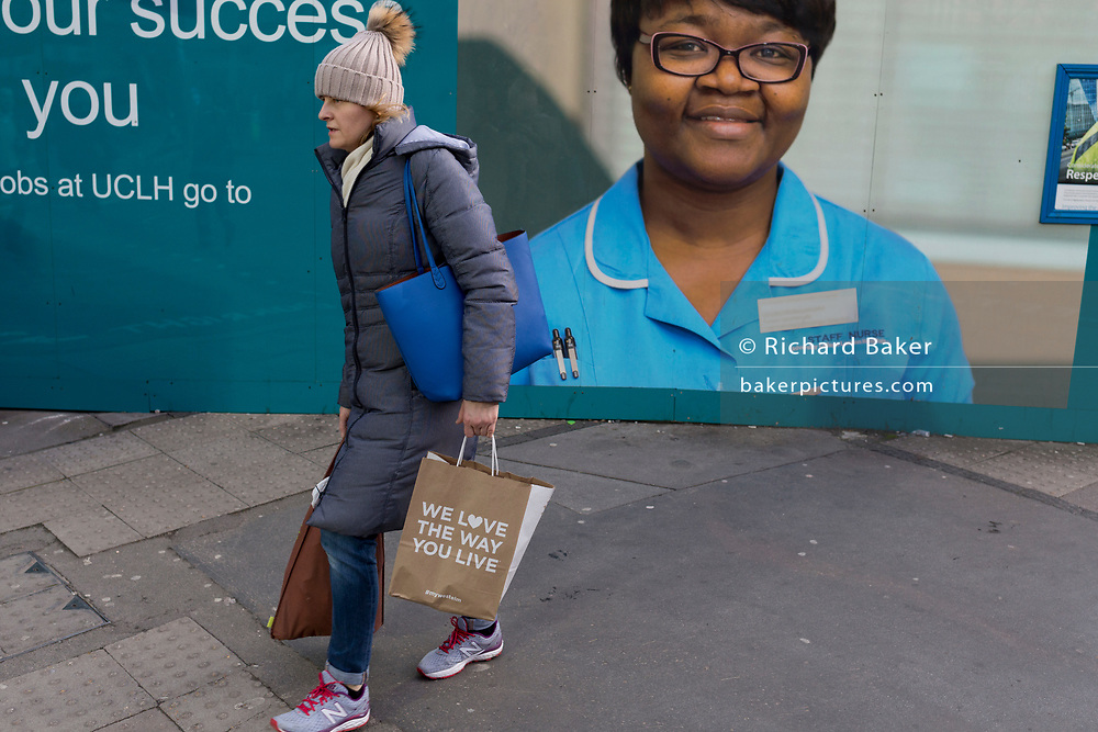 Carrying a bag with the words 'We love the way you live', a lady walks past the hoarding featuring the face of an NHS Staff Nurse employed at University College London, on 25th January 2018, in London, England.