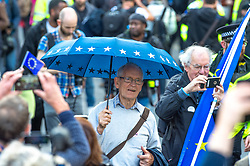 © Licensed to London News Pictures. 19/10/2019. London, UK. A man walks along Piccadilly holding a blue umbrella with gold stars at the People's Vote demonstration in central London. Photo credit: Peter Manning/LNP