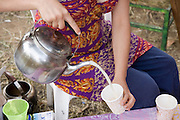 Young girl serving and selling chai, a hot spicy tea based beverage