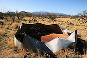 An old water tank for cattle sits on open range before a snow capped Mount Wrightson in the Santa Rita Mountains of the Coronado National Forest in the Sonoran Desert, Green Valley, Arizona, USA.