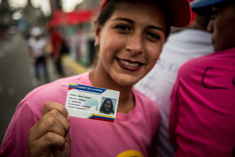 "CARACAS, VENEZUELA - JULY 27, 2017:  Breth Carrillo holds up her ""Carnet de la Patria"" (ID of the homeland) as she and other government supporters celebrate the final campaign rally for candidates for the election of the new constituent assembly, that will be held on July 30th. They marched and danced in the streets, as President Maduro and other socialist leaders addressed the large crowd. Opponents of the government criticize President Maduro for calling for this election - saying the new assembly is a power grab, and will be a puppet of the President - the only candidates on the ballot are government loyalists. Critics also fear the new assembly will re-write the constitution and wipe out the democratically elected and opposition controlled congress. There have been widespread reports of voter intimidation, and of the government threatening state workers and citizens that receive government benefits like subsidized food - who report the government telling them they are obligated to vote, and if they don't, they will lose their jobs and benefits. Thousands have taken to the streets to protest the election in the days leading up to the July 30th vote.  PHOTO: Meridith Kohut for The New York Times"