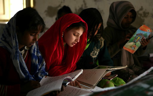 Children read from their books at a primary girls school in the Khairo Dero village in Larkana, Pakistan, on Wednesday, Jan. 23, 2008. Pakistan is seeking to sustain growth in a country where the government estimates a fourth of the population lives in poverty, or on less than a dollar a day.