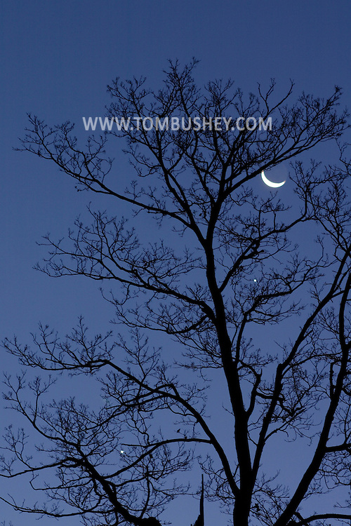 The crescent moon, top, Jupiter, center, and Venus, lower left, gather in the predawn sky on Nov. 9, 2004, in Middletown, N.Y.