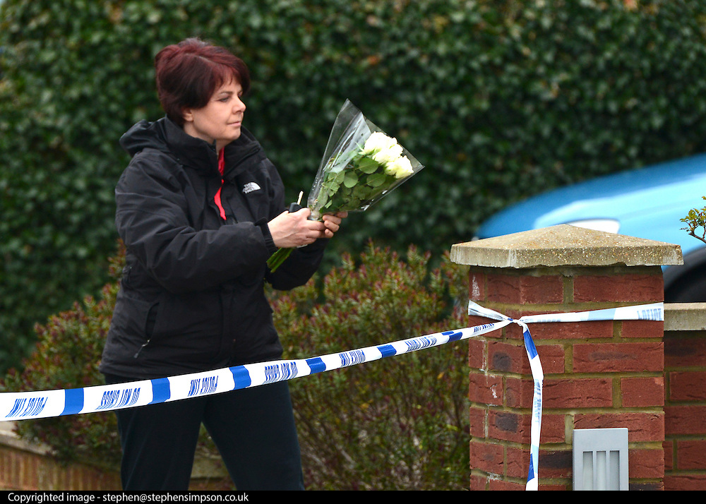 © Licensed to London News Pictures. 13/04/2013. Ruislip, UK A woman leaves flowers at the scene. Police and ambulance crews at the scene where a woman and two children have been found dead at a house in Ruislip, West London. Police were called by London Ambulance Service at approx 1840 hrs on Friday 12 April to reports of a woman and two children found deceased at an address in Midcroft Road. Photo credit : Stephen Simpson/LNP