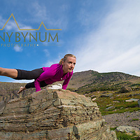 woman doing yoga hand balance on rock dramatic mountains