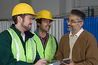 Cheerful men talking in factory