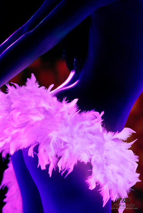 Sexy woman wearing a feather boa skirt on her behind.Black light