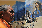 Border activist Rev. Mike Wilson of Tucson, Arizona, USA, walks in Altar, Sonora, Mexico, near a mural that depicts the journey of undocumented migrants crossing the border from Mexico in to the Arizona desert.  Wilson distributes water along the migrant trails in the Arizona desert.