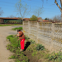 TIMISOARA, ROMANIA - APRIL 21:  A woman cleans a ditch next to her rural home on April 21, 2013 in Timisoara, Romania.  Romania has abandoned a target deadline of 2015 to switch to the single European currency and will now submit to the European Commission a programme on progress towards the adoption of the Euro, which for the first time will not have a target date. (Photo by Marco Secchi/Getty Images)