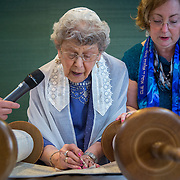 CHEVY CHASE, MD -MAY14: Charlotte Gottlieb, 93, reads from the Torah during her Bat-Mitzvah ceremony at the Five Star Residences in Chevy Chase, Maryland, May 14, 2016, as Dan Cohen and Cantor Susan Berkson look on. The women who were unable to have a Bat-Mitzvah ceremony at the traditional age of 13 because they were girls, are now finally able to celebrate this traditional Jewish coming of age ceremony. (Photo by Evelyn Hockstein/For The Washington Post)