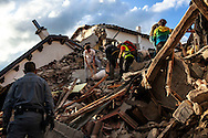 24 August 2016, Amatrice Italy - Rescuers carrying the lifeless body of a man pulled from the rubble after a 6.3 earthquake hit the town of Amatrice in Lazio region killing more than 240 people. Many other towns of the italian central regions have been hit by the quake. There are still many missing people under the rubble.