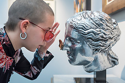 "© Licensed to London News Pictures. 16/01/2018. LONDON, UK. A staff member views ""Head of Venus"" by Clive Barker.  Preview day of the 30th anniversary of the London Art Fair.  The fair launches the international art calendar with modern and contemporary art from leading galleries around the world and is taking place at the Business Design Centre, Islington from 17 to 21 January 2018.   Photo credit: Stephen Chung/LNP"