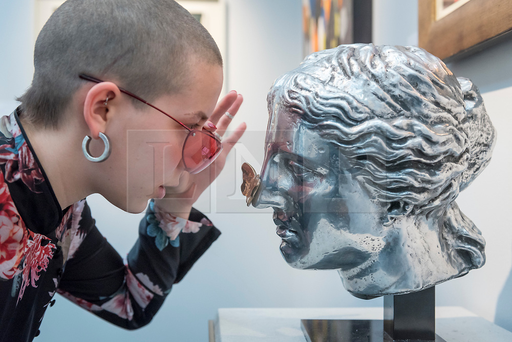 """© Licensed to London News Pictures. 16/01/2018. LONDON, UK. A staff member views """"Head of Venus"""" by Clive Barker.  Preview day of the 30th anniversary of the London Art Fair.  The fair launches the international art calendar with modern and contemporary art from leading galleries around the world and is taking place at the Business Design Centre, Islington from 17 to 21 January 2018.   Photo credit: Stephen Chung/LNP"""