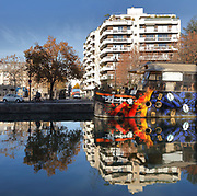 Large scale street art graffiti mural on the hull of the barge Grande Fantaisie, by the street artist Marko 93, at the Quai de l'Oise on the Canal de l'Ourcq in the 19th arrondissement of Paris, France. The mural depicts the dancer Sarah Guem beckoning a panther. The Canal de l'Ourcq is a 108.1km waterway begun in 1802 between Port-aux-Perches and the Canal Saint-Martin via the Bassin de la Villette or La Villette Basin. Picture by Manuel Cohen