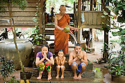 19 MARCH 2006 - SIEM REAP, SIEM REAP, CAMBODIA: A Buddhist monk pours holy water on a family during a blessing ceremony at a temple in the Angkor Wat complex near Siem Reap, Cambodia. Cambodian authorities estimate that more than one million tourists will visit Angkor Wat in 2006, making it the leading tourist attraction in Cambodia by a large margin. Angkor Wat is also a leading Buddhist worship site in Cambodia.  Photo by Jack Kurtz / ZUMA Press