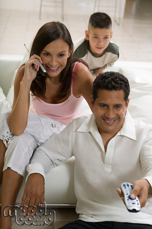 Family sitting on sofa watching TV mother on mobile phone