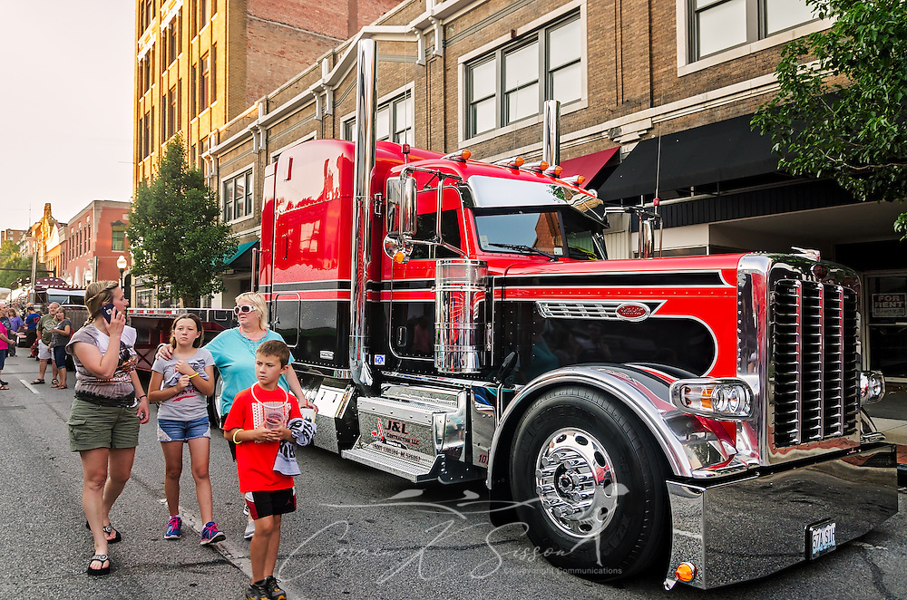 "Big rig enthusiasts walk past J&L Trucking's ""Northern Hospitality"" — a 2015 Peterbilt 389 Pride & Class with 2015 Etnyre trailer — during the 34th annual Shell Rotella SuperRigs parade , June 10, 2016, in Joplin, Missouri. SuperRigs, organized by Shell Oil Company, is an annual beauty contest for working trucks. Approximately 89 trucks entered this year's competition. ""Northern Hopitality"" took first place in the tractor/trailer category at SuperRigs. (Photo by Carmen K. Sisson/Cloudybright)"