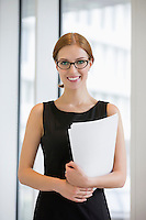 Portrait of confident businesswoman holding documents in office