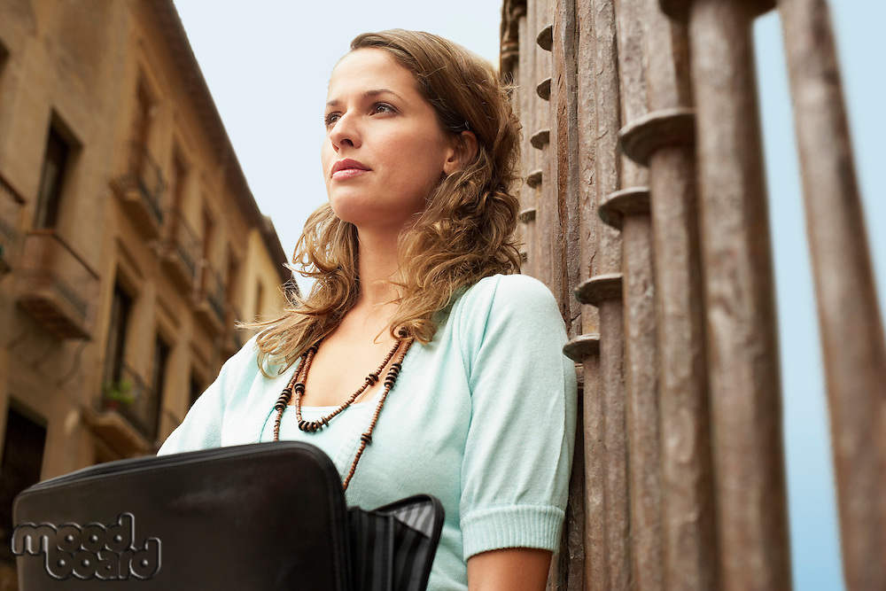 Woman holding briefcase leaning against railing low angle view.