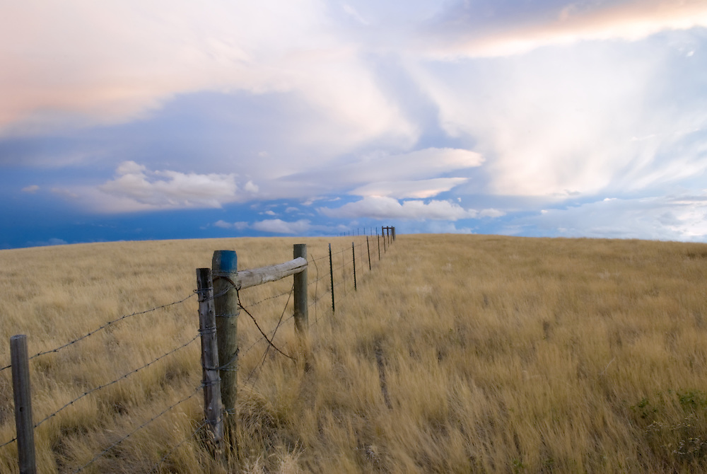 Dramatic sky over fenced ranching land.