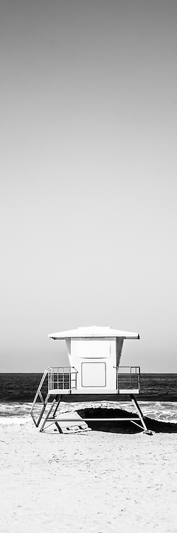 Lifeguard tower vertical panoramic picture in black and white. The lifeguard tower is located in Huntington Beach California. Panoramic picture ratio is 1:3. Image is Copyright © 2012 Paul Velgos with All Rights Reserved.