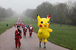 Windsor, UK. 24 November, 2019. Pikachu joins fun runners dressed as Santa Claus in the 2019 Windsor Santa Dash on the Long Walk in Windsor Great Park in aid of the Alexander Devine children's hospice.