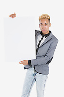 Portrait of a young man holding blank cardboard over gray background