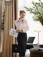 Business woman holding document standing in home office